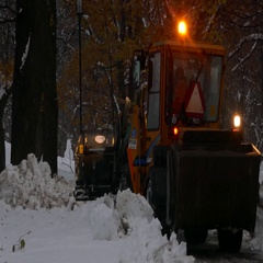 Excavator with snowplow clearing snow from road and turning to face the camera Stock Footage