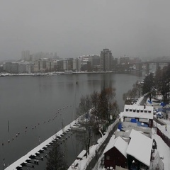 Aerial drone view of heavy snow on the city buildings and landscape near a river Stock Footage