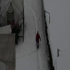 Man with a shovel walking in a small path walkway in a snowy day Stock Footage