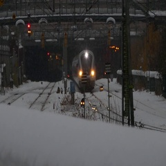 Train lights on coming out of a tunnel on a heavy snowy day - weather condition Stock Footage