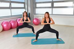 Fitness, sport, exercising lifestyle - female group doing yoga exercises at gym Kuvituskuvat
