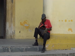 Afro-American man dressed red t-shirt, trousers, hat, glasses sits alone at the Stock Footage