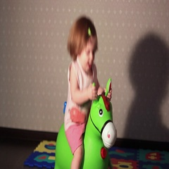 A child sits on a toy horse Stock Footage