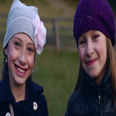 Two little beautiful girls look at the camera and smiling Stock Footage
