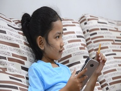 Close up shot of asian little girl using smartphont and eating biscuit Stock Footage
