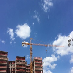 Crane on the background of a trace of the aircraft flying in the blue sky. Stock Footage