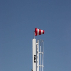 Red wind vane against a blue sky. Stock Footage
