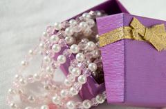 Ajar purple box with pink pearl strings Stock Photos