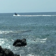 Ocean From Black Lava Rock Shore With Boat On Water Stock Footage