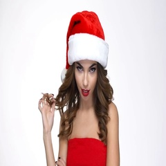 Woman in santa hat showing silence sign and winking Stock Footage