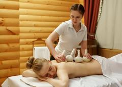 In spa. Masseuse puts salt bags on girl's back Stock Photos