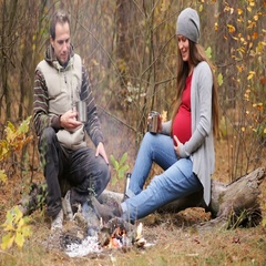 Pregnant woman with her husband resting by the fire Stock Footage