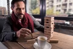 Happy amused man holding a wooden block Stock Photos