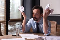 Hopeless miserable man holding crumpled paper Stock Photos