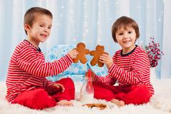 Two happy children eating cookies at christmas and drinking milk, laughing and t Kuvituskuvat