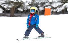 Cute little child, boy, learning to ski in Austrian ski resort, wintertime Stock Photos