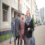 Woman in warm clothes and scarf walking down the street. Stock Footage