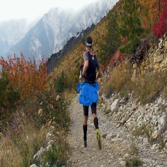 Two young male runners run from hill on a mountain trail Stock Footage