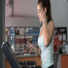 Attractive caucasian girl running on the treadmill in the sport gym with phone Stock Footage