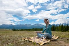 Woman in headphones listening music in a field and at the mountain Stock Photos
