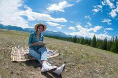 Young woman reading book and sitting in a field. Mountains background Stock Photos