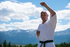 Man in white kimono and black belt training kung-fu, karate or aikido on Stock Photos