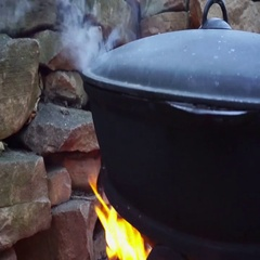Cooking meat on a fire in cast-iron cauldron Stock Footage