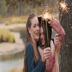 Teenage girls with sparklers celebrate and laugh. Close portrait. Autumn outdoor Stock Footage