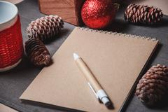 Notebook in the center of cute Christmas decoration, cones Stock Photos