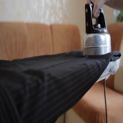 Hand ironing black trousers on the ironing board, close-up Stock Footage