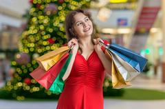 Young happy woman is shopping gifts for Christmas. Kuvituskuvat