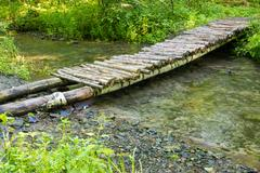 Wooden bridge over a small river forest Stock Photos