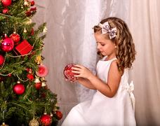 Child decorate on Christmas tree home alone. Stock Photos