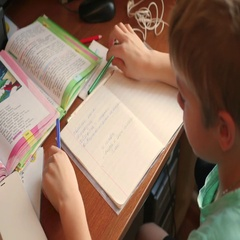 The child does his homework, writes in a copybook at table Stock Footage