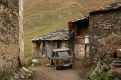Medieval village of Svan people and old car in Georgia Stock Photos