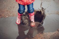 Child wearing pink rain boots jumping into a puddle Stock Photos