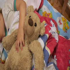 The sweet baby sleeps in a cot with a teddy bear Stock Footage