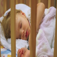 The sweet baby sleeps in a cot with a teddy bear. Stock Footage