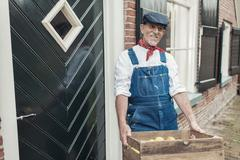 Traditional retro greengrocer in dungarees delivering fresh apples at farm. Stock Photos