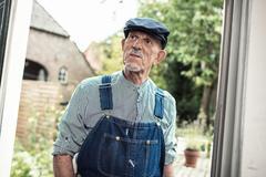 Vintage senior farmer wearing dungarees and cap entering front door of farm. Stock Photos