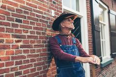 Senior farmer in dungarees with hat standing against wall of farm. Stock Photos