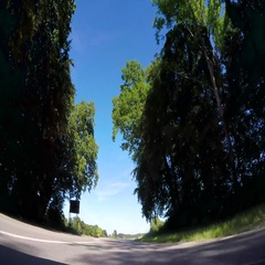 Vehicle drive POV car travel countryside road green grass trees lowland blue sky Stock Footage