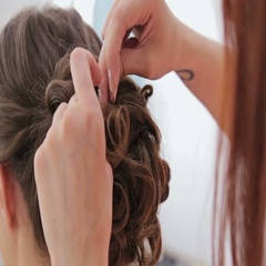 Close up shot. Hairdresser finishing hairstyle for young pretty woman Stock Footage