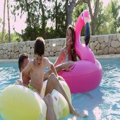 Family Having Fun On Inflatables In Outdoor Swimming Pool Stock Footage