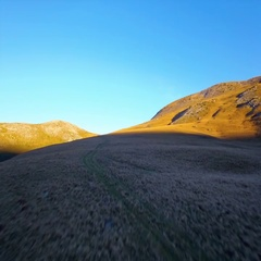 Beautiful scenery grassland mountain aerial low grass remote landscape blue sky Stock Footage