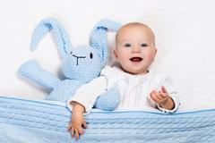 Funny little baby wearing a warm knitted jacket playing with toy bunny Stock Photos