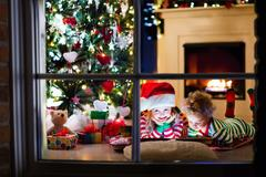 Happy little kids in red and green striped pajamas decorate Christmas tree Stock Photos