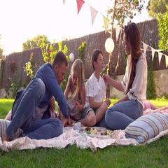 Family Enjoying Picnic On Blanket In Garden Stock Footage
