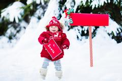 Happy child holding letter to Santa at red mail box in snow forest. Stock Photos