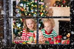 Little boy and girl making Christmas gingerbread house at fireplace Stock Photos